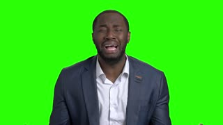 Desperate businessman crying on green screen. Afro american man in business suit in full despair on Alpha Channel background.