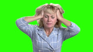Desperate mature woman on green screen. Stressed caucasian woman on chroma key background. Concept of nervous breakdown.