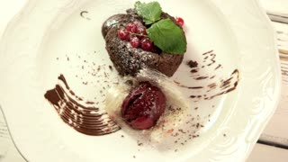 Dessert with red berries. Mint leaves and powdered sugar. Sweet chocolate filling.