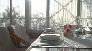 Dining table under sunlight. Empty wineglasses and flower vase. Restaurant business ideas.