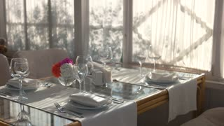 Dinner table and chairs. Tablecloth, silverware and plates.