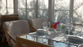 Dinner table near window. Cutlery plates and glasses.