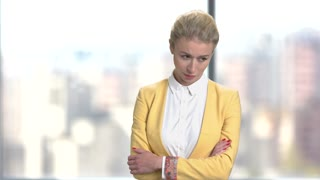 Displeased business woman on blurred background. Young exhausted business lady with arms crossed. Tired waiting for somebody.