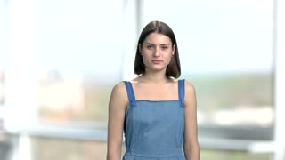 Dissatisfied young woman, blurred background. Attractive young woman in denim clothes looking sad. Human emotions of sadness.