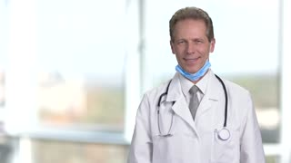 Doctor in white uniform crossing arms. Mature man working as doctor in hospital. Abstract blurred background in bright room.
