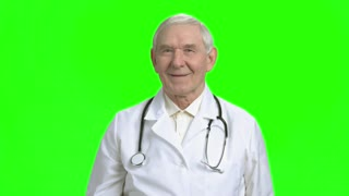 Doctor showing thumb up. Cheerful old doctor showing thump up, background for keying.