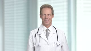 Doctor with pills gesturing thumb up. Male cheerful physician showing blister pack pills, blurred background. Mature successful medical specialist. Pharmaceutical and medicine concept.