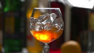 Drink slowly pouring into glass. Orange liquid with ice cubes. Bartender makes aperol spritz. Add water to cocktail.