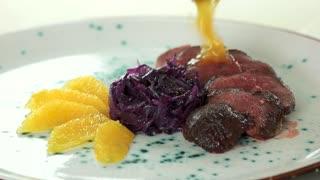 Duck breast dish. Tasty food, orange sauce.
