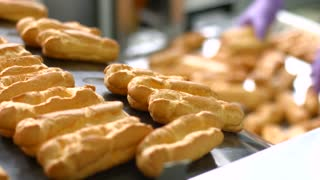 Eclairs sliding down conveyor line. Production of eclairs. High standard of quality. Making the best confectionery.