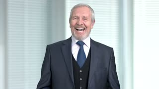 Elderly businessman laughing on blurred background. Senior male executive is laughing.