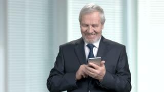 Elderly businessman sending a text message. Elegant handsome male entrepreneur dressed in formal wear texting messages via smartphone, blurred background.