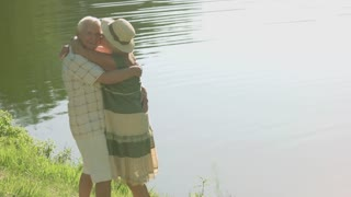 Elderly couple hugging near river. Amusing couple of seniors having rest near water. Key for saving love for many years.