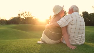 Elderly couple kissing on green grass. Seniors enjoying of nature, sunny day. Affection and romance between old couple.