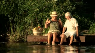Elderly couple sitting at lake. Old woman dangling with legs in river. Senior family enjoying of summer rest.