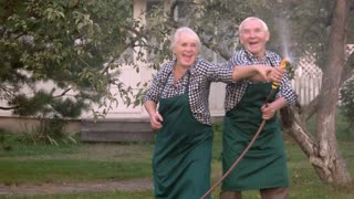 Elderly couple with garden hose. Old people having fun.