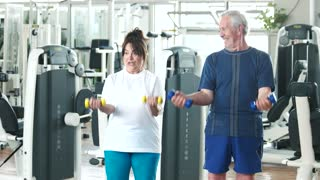 Elderly couple working out at gym. Happy senior man and woman lifting dumbbells at gym. Beautiful elderly people at fitness club.
