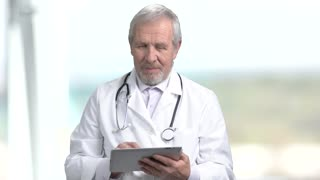 Elderly doctor typing on pc tablet. Senior male doctor using computer tablet on blurred background. People, profession, technology.