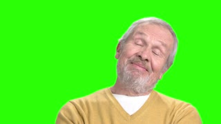 Elderly dreaming man, green screen. Positive mature man on chroma key background. Human facial expressions.