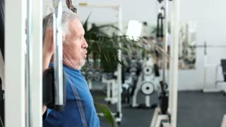 Elderly fitness athlete doing chest exercises. Senior man training at gym, side view.