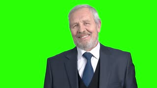 Elderly flirting businessman, green screen. Senior man in grey suit smiling and looking at camera, chroma key background.