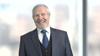 Elderly laughing entrepreneur, slow motion. Joyful senior man in formal wear, blurred background. Human facial expression.