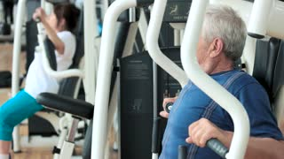 Elderly male person training at gym. Senior man exercising on machine at fitness club, side view. Active way of life.