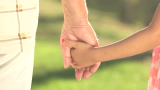 Elderly man and child holding hands outdoors. Close up girl and her grandfather holding hands on a walk, nature background. Girl hugging grandfather hand with two hands. Family values concept.