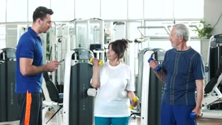 Elderly man and woman at gym. Young trainer helping to senior woman lifting dumbbell. Sport and healthcare.