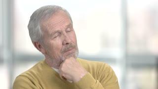 Elderly man dreaming on blurred background. Thinking retired man recalling his memories. Portrait of cheerful elderly man.