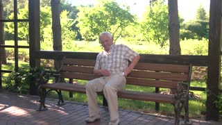 Elderly man eating medicine. Senior guy on park bench. I need some pills. Painkillers always at hand.