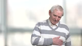 Elderly man experiencing discomfort in his chest. Old man feeling bad, blurred background. Heart problems concept.