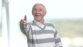Elderly man giving thumbs up. Smiling european pensioner showing two thumbs up, blurred background.