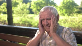 Elderly man holds his head. Senior male has headache. Impact of constant stress. High blood pressure.