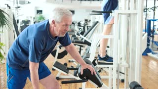 Elderly man lifting dumbbell at modern gym. Smiling senior man working out with weight at fitness center. Retirement and sport.