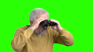 Elderly man with binoculars, green screen. Senior man looking with binoculars, alpha channel background.