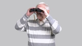 Elderly man with binoculars, grey background. Aged man in casual sweater looking through binoculars. Retired man with binoculars.