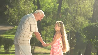 Elderly man with grandchild having communication. Grandfather with his granddaughter talking in park, summer nature background.