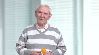 Elderly man with medication, blurred background. Senior man holding prescription bottle with pills, blurred background.