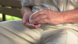 Elderly man's hand with pills. White bottle with medicine. Minerals for bone health. Few capsules per day.