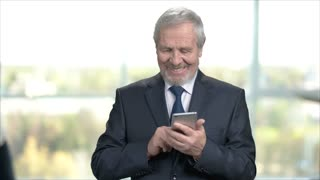 Elderly smiling businessman using smartphone. Cheerful older buinessman texting a message on his smartphone while standing on office background. People, business, emotions.