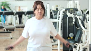 Elderly woman jumping with skipping rope. Senior woman exercising at gym. Active way of life.
