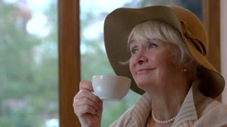 Elderly woman with cup smiling. Lady drinking coffee indoors. Positive thinking tips.