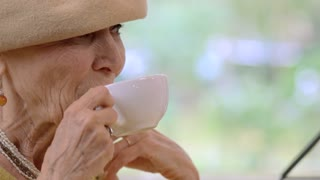 Elderly woman with cup talking. Old lady drinking coffee. Confidence and persuasion.