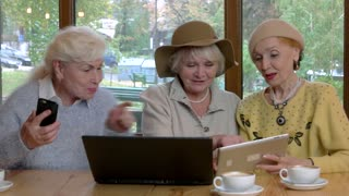 Elderly women with gadgets. Ladies at cafe table smiling. Simplicity of social networking.