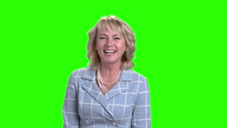 Elegant woman is laughing on green screen. Joyful middle-aged business lady on chroma key background. Human expression of happiness.