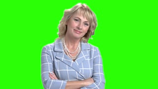 Elegant woman smiling on chroma key background. Pretty mature blonde posing with arms crossed on green screen. Portrait of successful business lady.