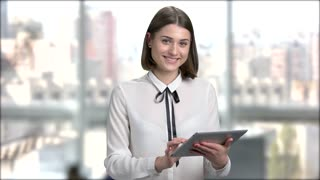 Elegant young woman using digital tablet. Young business woman check email on the digital tablet and smiling on blurred background.