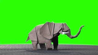 Elephant origami miniature on green screen. Traditional paper elephant on chroma key background. Wet-folding technique.