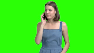 Emotional energetic woman talking on phone, front view. Green screen hromakey background for keying.